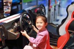 Menina asiática pequena feliz da criança que joga o jogo de vídeo da arcada Carro competindo imagens de stock royalty free