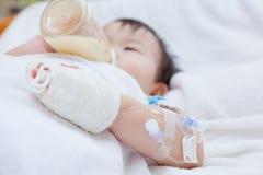Menina asiática pequena que encontra-se em uma cama médica Imagens de Stock Royalty Free