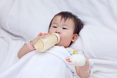 Menina asiática pequena que encontra-se em uma cama médica Fotos de Stock