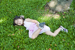 Menina asiática pequena que encontra-se na grama verde. Imagem de Stock Royalty Free