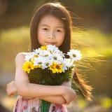 Menina asiática pequena que guarda um grupo de flores Fotografia de Stock Royalty Free