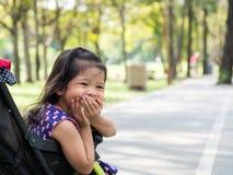 Menina asiática pequena que senta-se em um carrinho de criança no parque público Olha happly e rir e amordaçar imagens de stock royalty free