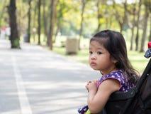 Menina asiática pequena que senta-se em um carrinho de criança no parque público Os olhos da menina olham como a vista de alguém fotos de stock