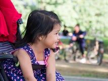 Menina asiática pequena que senta-se em um carrinho de criança no parque público Tem ser menina asiática do smileLittle que senta imagem de stock