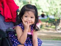 Menina asiática pequena que senta-se em um carrinho de criança no parque público Tem ser sorriso e amor na linguagem gestual foto de stock