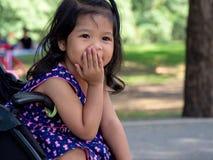 Menina asiática pequena que senta-se em um carrinho de criança no parque público Tem ser sorriso e amor na linguagem gestual fotografia de stock