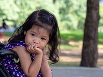 Menina asiática pequena que senta-se em um carrinho de criança no parque público Tem ser sorriso e amor na linguagem gestual fotos de stock