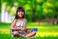 Menina asiática pequena que senta-se na grama e na uquelele do jogo Imagens de Stock