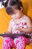 Menina asiática pequena que usa a tabuleta digital, ponto do dedo da criança no co Imagens de Stock