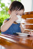 Menina asiática pequena (tailandesa) que bebe de um copo Imagem de Stock