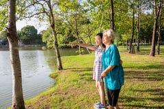 Menina asiática que apoia a mulher superior com vara de passeio, a avó de sorriso feliz e a neta no parque exterior, idoso fotografia de stock