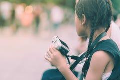 Menina asiática que aprende usar uma câmera mirrorless com sua mamã no parque público imagens de stock