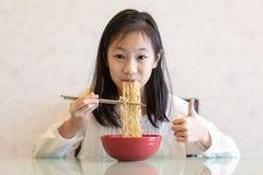 Menina asiática que come macarronetes na tabela fotografia de stock