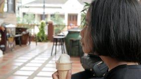 Menina asiática que come o gelado com profundidade do foco seleto da felicidade de campo rasa video estoque