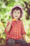 Menina asiática que come o gelado no verão na parte traseira borrada da natureza Imagens de Stock Royalty Free