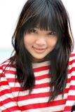 Menina asiática que desgasta o sorriso colorido das listras imagens de stock
