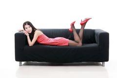 Menina asiática que encontra-se no sofá. Fotografia de Stock
