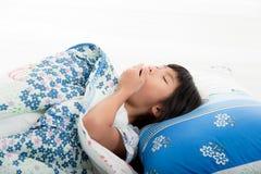 Menina asiática que encontra-se sob uma cobertura na cama fotos de stock