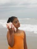 Menina asiática que escuta o conch Imagem de Stock Royalty Free