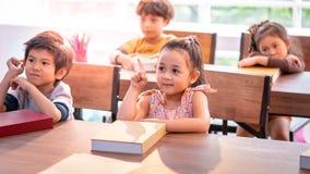 Menina asiática que estuda na sala de aula do jardim de infância foto de stock