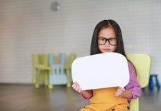 Menina asiática que guarda a bolha vazia vazia do discurso para dizer algo na sala de aula com vista em linha reta na câmera Educ foto de stock