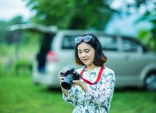 Menina asiática que guarda e que verifica a foto da câmera Foto de Stock Royalty Free