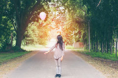 Menina asiática que guarda um balão no parque Foto de Stock