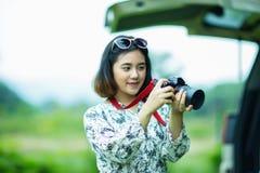 Menina asiática que guarda uma câmera e que verifica a foto Imagem de Stock Royalty Free