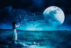 Menina asiática que joga com bolhas de sabão Lua super atrás de parcial fotografia de stock royalty free