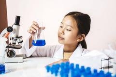 Menina asiática que joga como um cientista para experimentar Imagem de Stock Royalty Free