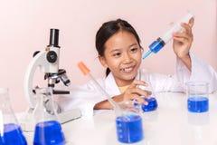 Menina asiática que joga como um cientista para experimentar com o equipamento de laboratório Fotos de Stock
