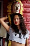 Menina asiática que levanta contra um fundo de uma parede vermelha Foto de Stock Royalty Free