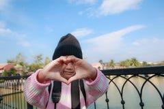 A menina asiática que mostra a mão faz-me a forma do coração com felicidade Imagem de Stock