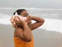 Menina asiática que ouve o conch Fotos de Stock