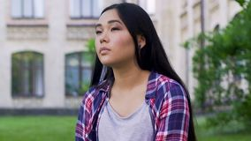 Menina asiática que senta-se apenas e que olha ao redor, personalidade sonhadora, pensativa video estoque