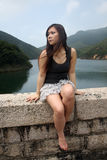 Menina asiática que senta-se fora foto de stock royalty free