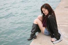 Menina asiática que senta-se na borda fotos de stock royalty free