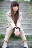 Menina asiática que senta-se nas escadas Imagem de Stock