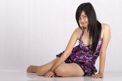 Menina asiática que senta-se no assoalho Fotografia de Stock