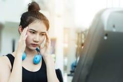 Menina asiática que tem a dor de cabeça da enxaqueca ao dar certo no gym Fotografia de Stock Royalty Free