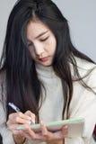 Menina asiática que toma notas Imagem de Stock