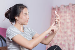 Menina asiática que usa a câmera dianteira do telefone para tomar a foto ela mesma fotos de stock royalty free
