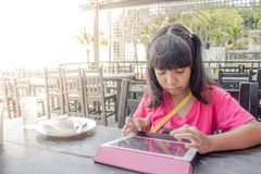Menina asiática que usa a tabuleta no restaurante fotografia de stock