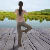 A menina asiática senta na meditação a borda do ` s da água Ioga exterior concentrada imagem de stock