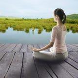 A menina asiática senta na meditação a borda do ` s da água Ioga exterior concentrada foto de stock royalty free