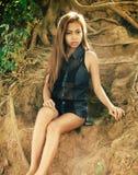 Menina asiática 'sexy', bonita nova que senta-se na terra do monte Imagens de Stock