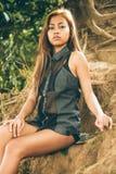 Menina asiática 'sexy', bonita nova que senta-se na terra do monte Imagens de Stock Royalty Free