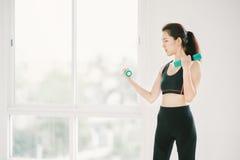 Menina asiática 'sexy' que exercita com pesos no gym da aptidão com espaço da cópia, esporte e conceito saudável do estilo de vid Imagem de Stock
