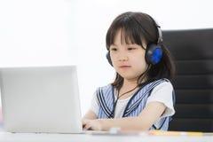 A menina asiática veste o fones de ouvido imagem de stock royalty free