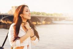 Menina asi?tica feliz do cabelo longo bonito positivo na camisa branca no fundo da ponte do rio da cidade, tempo de f?rias do cur fotografia de stock royalty free